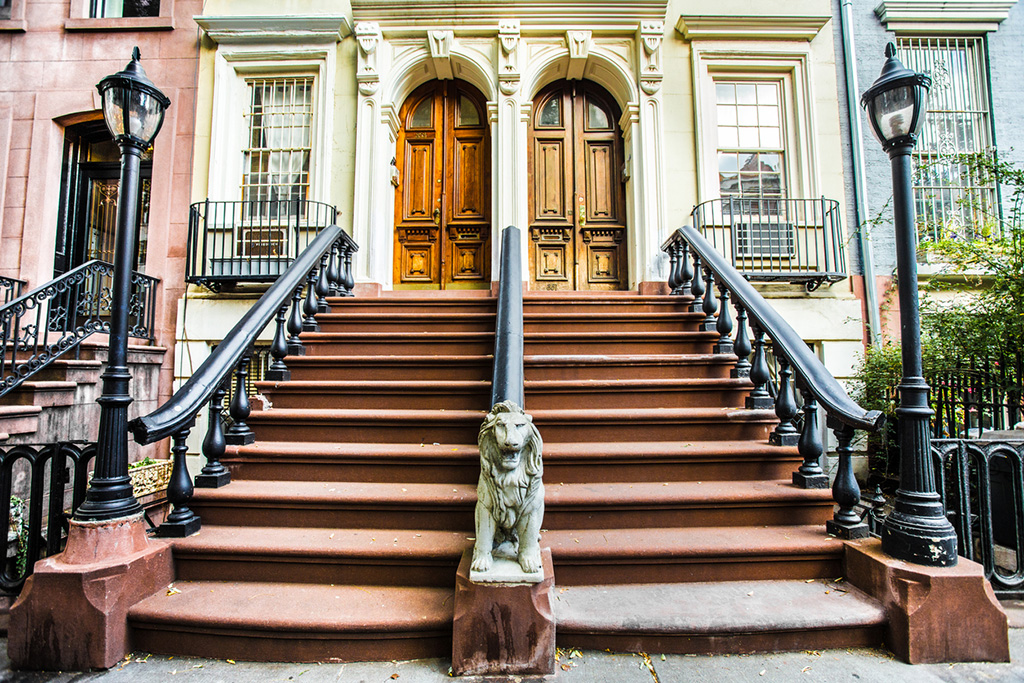 New York City, New York, USA - October 25, 2013: New York City sidewalk scene of steps leading to urban homes with wooden doors. These home are typical of architecture in the Chelsea section of Manhattan.
